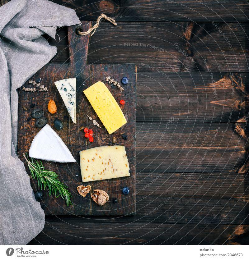 Stücke von verschiedenen Käsesorten Tisch Holz alt Essen blau gelb weiß Holzplatte Brie roquefort Cheddar Verschiedenheit Lebensmittel Mahlzeit Snack