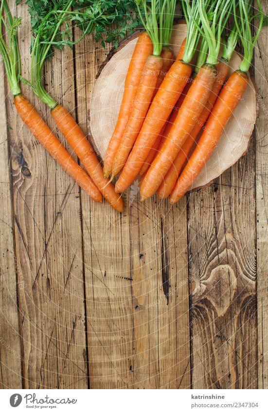 Frische rohe Karotten mit Blättern auf einem Holztisch Gemüse Ernährung Vegetarische Ernährung Blatt frisch braun grün Möhre Landwirt Lebensmittel Ernte