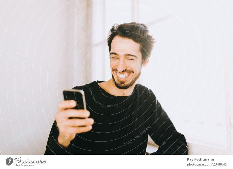 young man reading text message on his cellphone Lifestyle Reichtum Freude Glück Sommer Häusliches Leben Wohnung Kapitalwirtschaft Handy maskulin Junger Mann