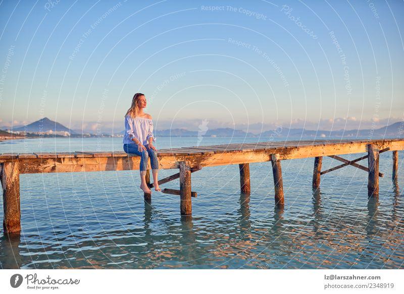 Barfuß-Frau, die bei Sonnenuntergang auf einem Küstenpier sitzt. Lifestyle Glück schön Freizeit & Hobby Ferien & Urlaub & Reisen Freiheit Sommer Strand Meer