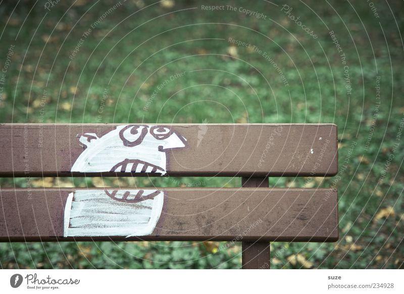 Bankangestellter Wiese Holz Graffiti lustig braun grün Sitzgelegenheit verbissen Schmiererei außergewöhnlich skurril durchbeißen Kopf Strukturen & Formen Humor