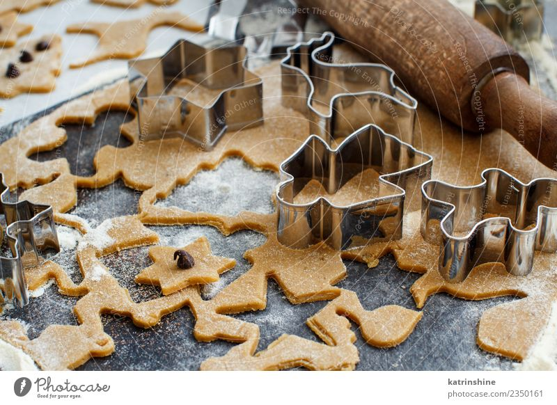 Weihnachtskekse mit Keksausstechern auf einem dunklen Tisch zubereiten. Teigwaren Backwaren Dessert Winter Küche Metall machen braun weiß Tradition backen