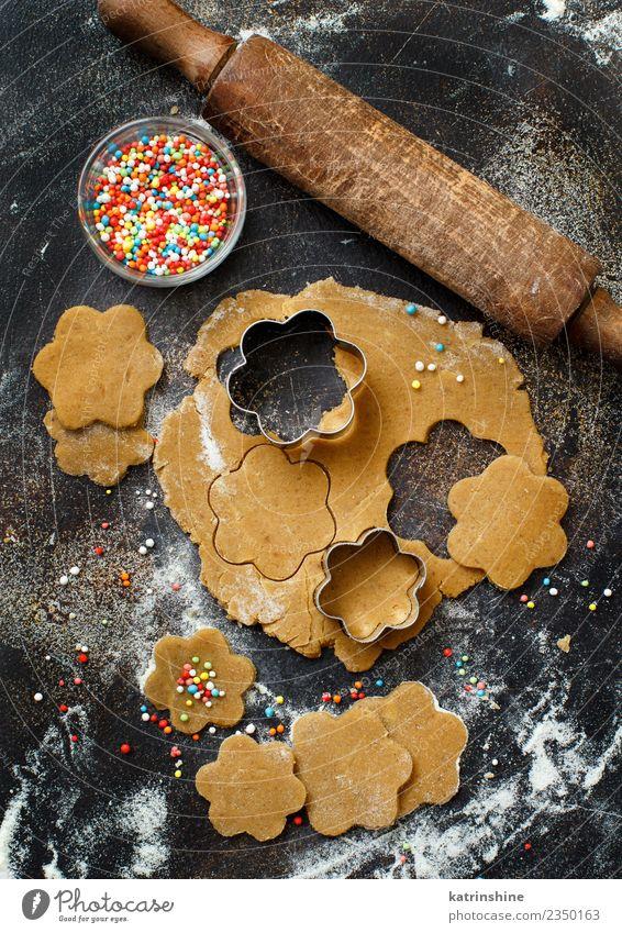 Kekse mit Keksausstechern auf einem dunklen Tisch zubereiten. Teigwaren Backwaren Dessert Küche Blume Metall machen oben braun Tradition backen Bäckerei Biskuit