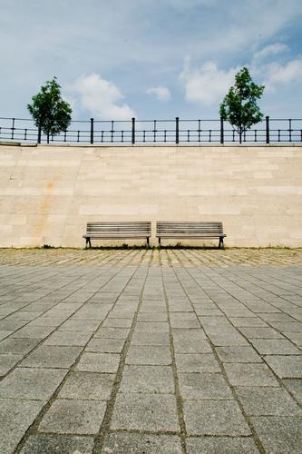 zwei mal zwei Mauer Wand Sauberkeit Zufriedenheit Bank Sitzgelegenheit Parkbank Baum Geländer Boden Steinboden Pflastersteine paarweise 2 doppelt gemoppelt