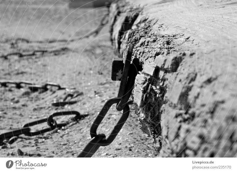...in chains... Sand Küste Strand Stahl alt dunkel Schwarzweißfoto Außenaufnahme Menschenleer Tag Kontrast Sonnenlicht Kette Befestigung Holz