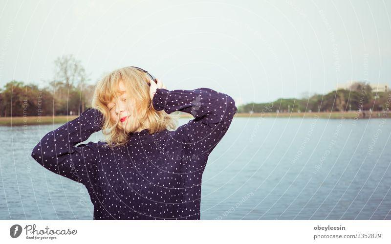 Junges hübsches Mädchen, das Spaß daran hat, Musik über Kopfhörer zu hören. Lifestyle Stil Freude Glück schön Erholung Freizeit & Hobby Sommer Telefon