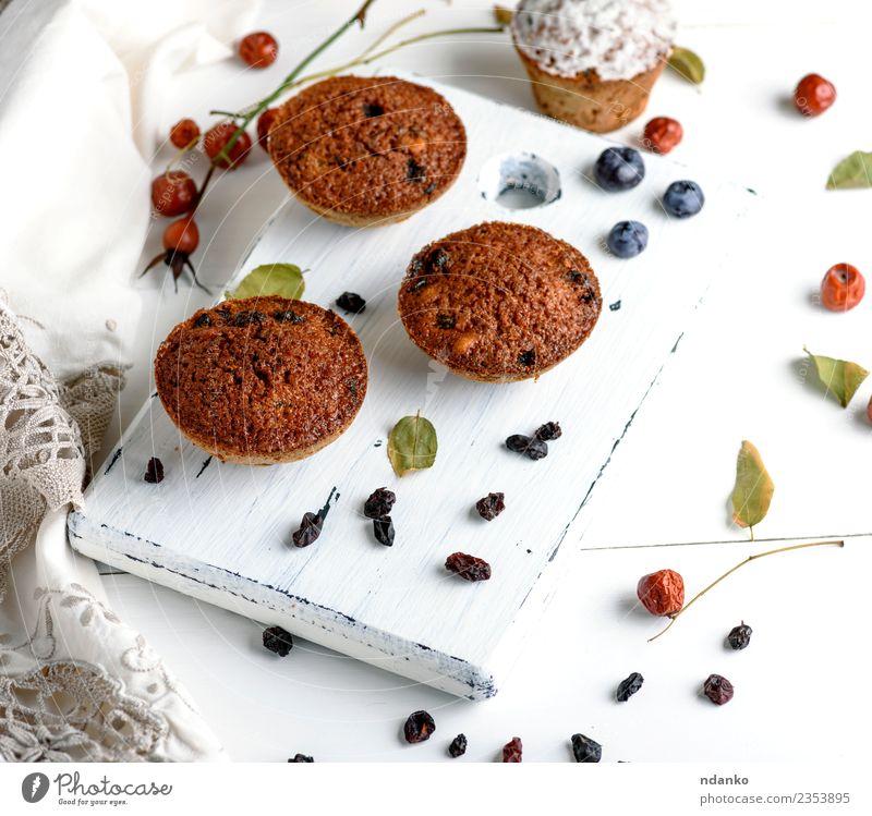 Törtchen mit Trockenfrüchten Kuchen Dessert Ernährung Frühstück Tisch Holz Essen frisch klein oben braun weiß Hintergrund backen Bäckerei Schokolade