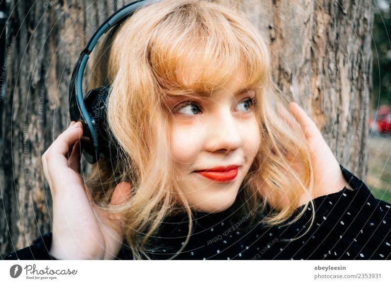 Junges hübsches Mädchen, das Spaß daran hat, Musik über Kopfhörer zu hören, Lifestyle Stil Freude Glück schön Erholung Freizeit & Hobby Sommer Telefon
