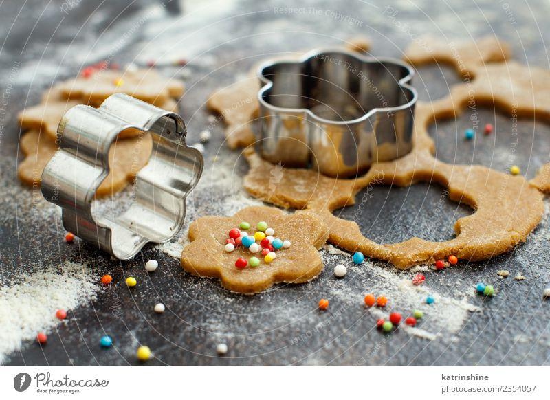 Kekse mit Keksausstechern auf einem dunklen Tisch zubereiten. Teigwaren Backwaren Dessert Küche Blume Metall machen braun Tradition backen Bäckerei Biskuit