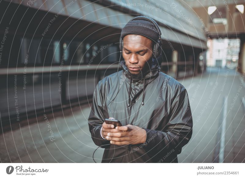 Junger Mann hört Musik mit seinen Kopfhörern. Lifestyle Freizeit & Hobby Ferien & Urlaub & Reisen Ausflug Telefon Handy Technik & Technologie