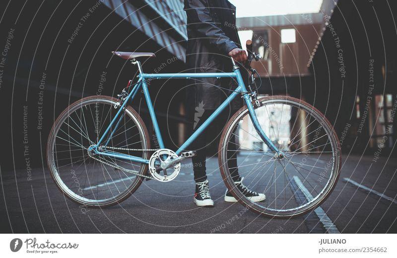 Junger Mann hält blaues Fahrrad in der Stadt. modern Stadtleben Großstadt Schlittschuhlaufen Lifestyle Hipster Schickimicki Mode Bekleidung Jacke erwärmen