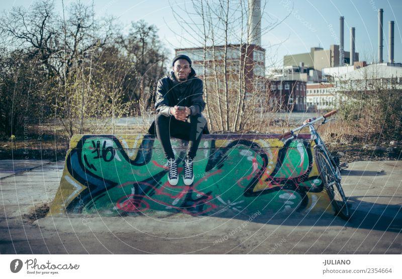 Der junge moderne Hipster sitzt auf einer Halfpipe im Skatepark. Stadt Stadtleben Großstadt Fotokamera Schlittschuhlaufen Skateplatz Lifestyle Schickimicki