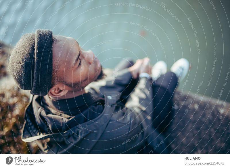 Junger Mann, der am Hafen sitzt und das Wasser hinunterschaut. Lifestyle Mensch Jugendliche 13-18 Jahre 18-30 Jahre Erwachsene Frühling schlechtes Wetter Wind