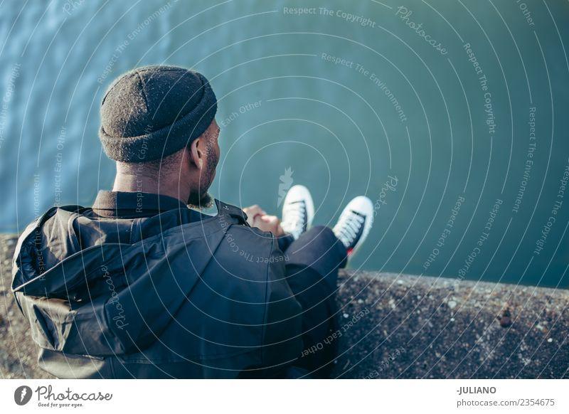 Junger Mann, der am Hafen sitzt und auf das Wasser schaut. Lifestyle Mensch Jugendliche 13-18 Jahre 18-30 Jahre Erwachsene Frühling schlechtes Wetter Wind Hut