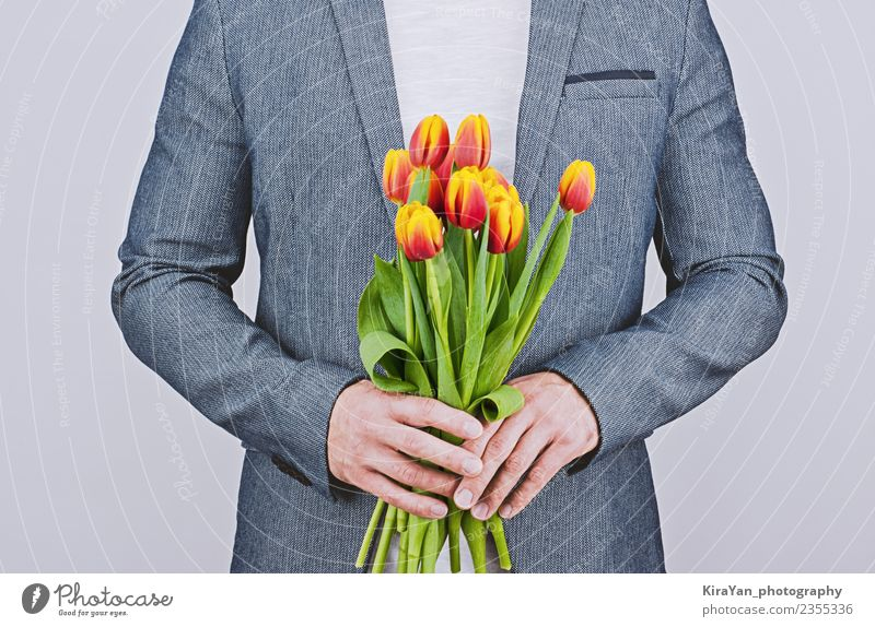 Mann in blauer Jacke mit Tulpenstrauß Glück schön Flirten Feste & Feiern Valentinstag Mensch Erwachsene Mutter Blume Vollbart Blumenstrauß Liebe gelb rot weiß