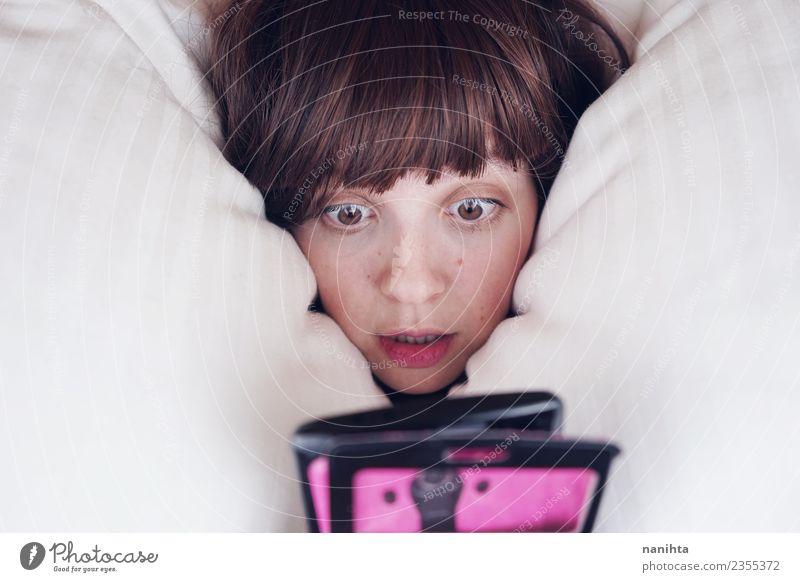 Junge Frau, die nicht schlafen kann, benutzt ihr Handy. Lifestyle Stil schön Haut Gesicht Freizeit & Hobby Bett Technik & Technologie Unterhaltungselektronik