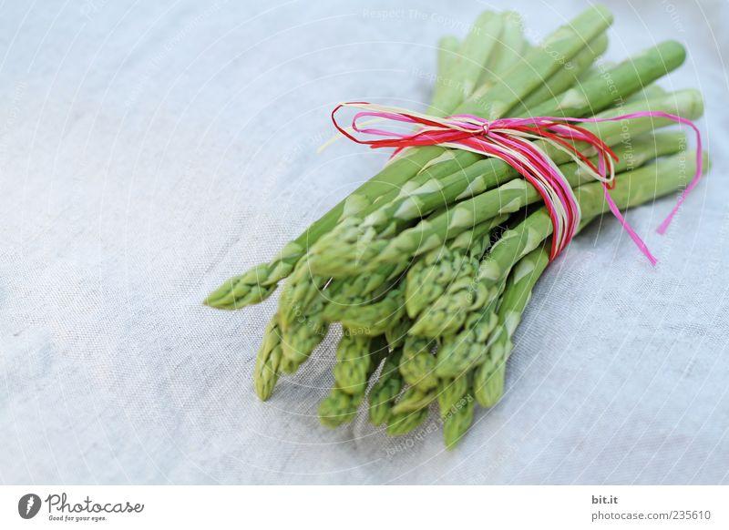 EIne Portion Spargelspitzen vom grünen Spargel, frisch geerntet vom einheimischen Feld, liegt zusammen gebunden, mit einem Band mit Schleife dekoriert, aus Bast, auf dem Tisch mit weissem Leinentuch.