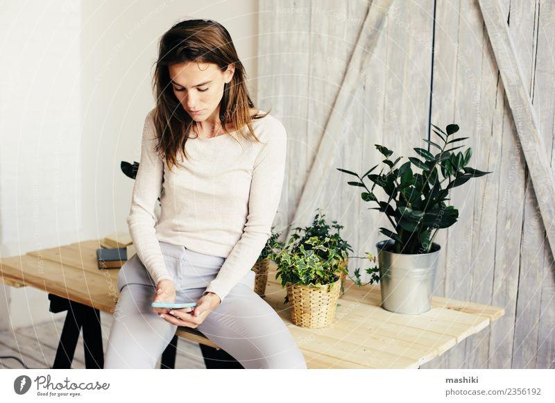 junge Frau SMS-Nachricht Lifestyle Tisch Wohnzimmer Erwachsene Pflanze Blume Mode modern lässig Hipster Zimmerpflanze Blumentopf Gärtner Pflege Growh