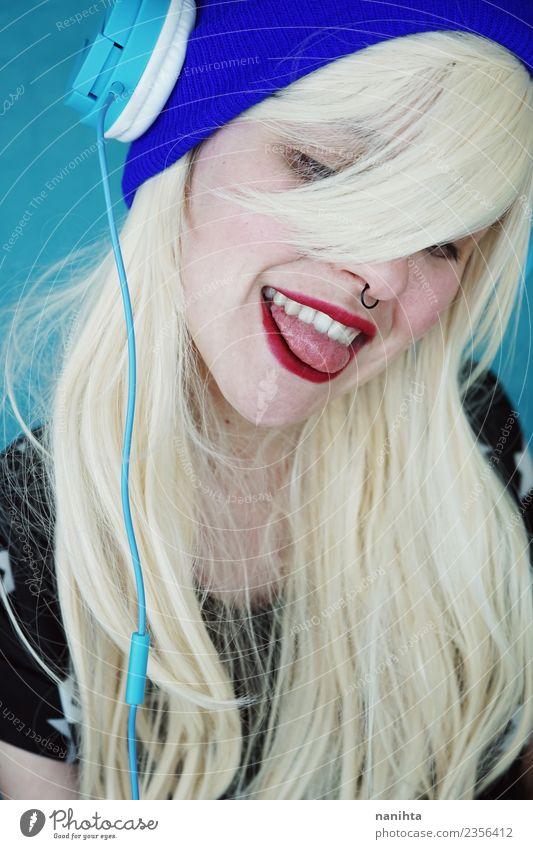 Junge und blonde Frau, die ihre Zunge herausstreckt. Lifestyle Stil Design Freude schön Haare & Frisuren Haut Gesicht Freizeit & Hobby Headset