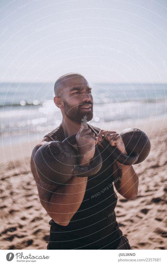 Der Sportler macht ein Wasserkochglocken-Training am Strand. Junger Mann Fitness Sport-Training hart transpirieren Muskulatur Freude Geschwindigkeit positiv