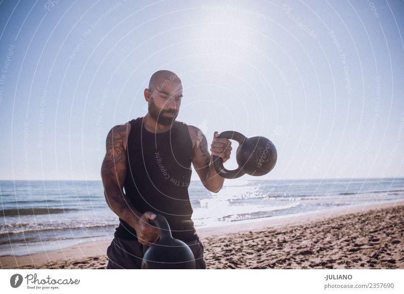 Der Sportler macht ein Wasserkochglocken-Training am Strand. Junger Mann Fitness Sport-Training Berufsausbildung hart transpirieren Muskulatur Freude