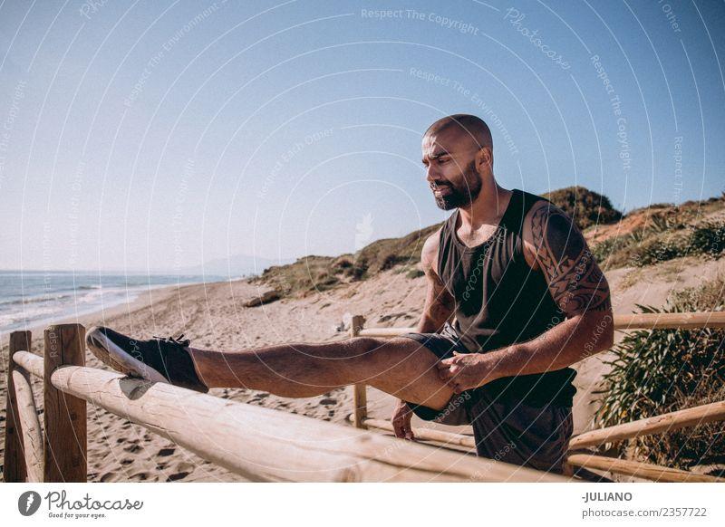 zäher muskulöser Mann streckt sich am Geländer zum Strand. Junger Mann Sport Training Fitness Sport-Training hart transpirieren Muskulatur Freude Sportler