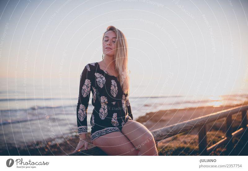 Junges Mädchen sitzt und genießt den Blick auf den Sonnenuntergang am Meer. Strand blond Coolness Abenddämmerung Freude Güte lachen Lifestyle retro Sand Lächeln