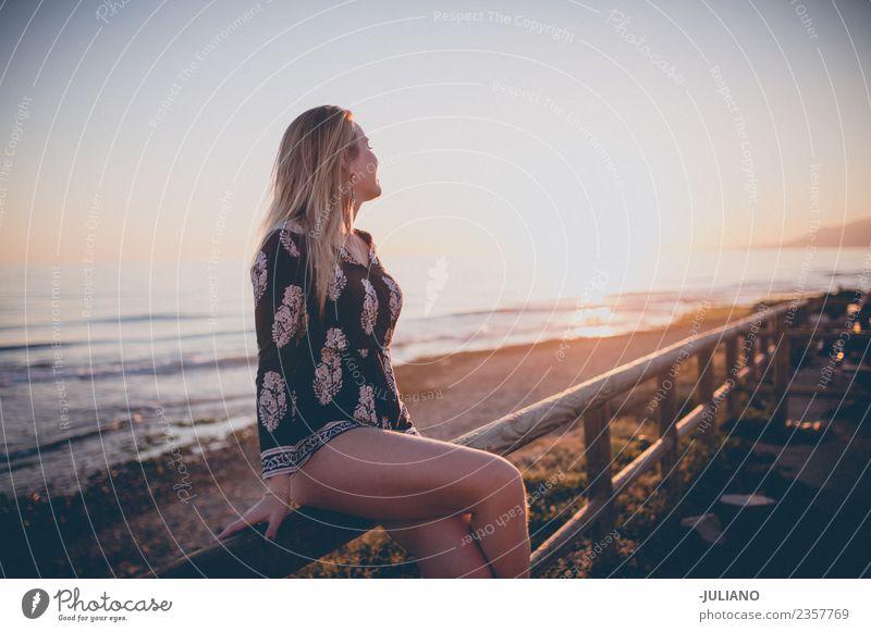 Junge Frau, die auf einem Geländer sitzt und den Sonnenuntergang am Meer beobachtet. Strand blond Coolness Abenddämmerung Freude Mädchen gut Güte lachen