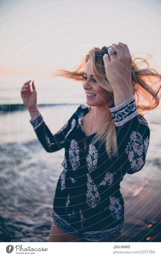 Junge Frau am Strand, während der Sonnenuntergang lächelt. blond Coolness Abenddämmerung Freude Mädchen gut Güte lachen Lifestyle Meer retro Sand Lächeln Sommer
