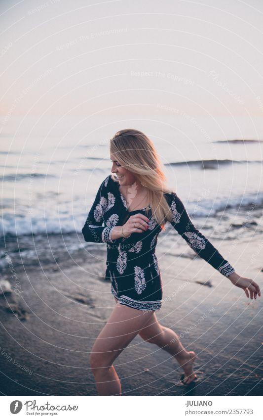 Junge Frau am Strand, die am Meer rennt und lacht. Sonne blond Coolness Abenddämmerung Freude gut Güte lachen Lifestyle retro Sand Lächeln Sommer