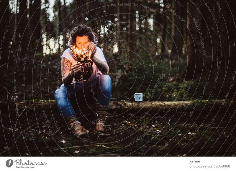 Frau mit brennender Wunderkerze auf Baumstamm im Wald. Eine Emaille-Tasse steht neben ihr. Lifestyle harmonisch Wohlgefühl Sinnesorgane Erholung ruhig