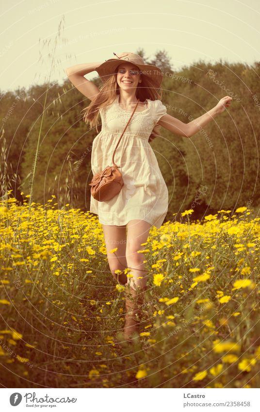 Junge lächelnde Frau, die in ein Feld von Gänseblümchen springt. Lifestyle Freude Leben Freizeit & Hobby Ferien & Urlaub & Reisen Freiheit Mensch feminin