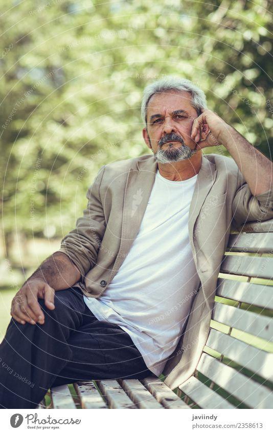 Nachdenklicher reifer Mann, der auf einer Bank in einem Stadtpark sitzt. Lifestyle Glück Ruhestand Mensch Erwachsene Männlicher Senior 1 45-60 Jahre