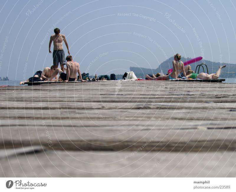 Auf dem Steg Holzbrett Mann Frau Bikini Italien See Meer San Felice del Benaco Gardasee Europa Mensch Jugendliche Bademoden Schwimmshorts Sonne Wasser