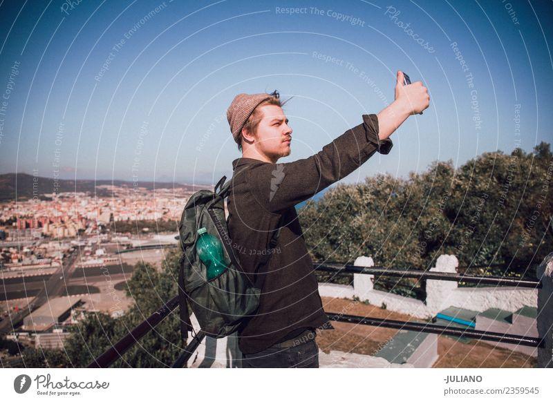 Junger Mann nimmt Selfie an der Spitze der Stadt. Abenddämmerung Gefühle Glück Leben Lifestyle Sommer Sonne Sonnenuntergang Jugendliche Abenteuer Freiheit