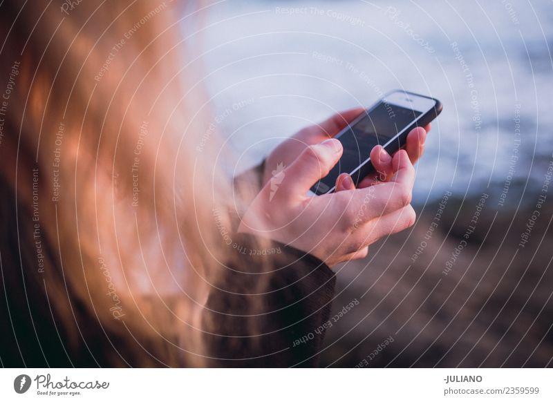 Junge Frau hält Smartphone in den Händen am Strand. Abenddämmerung Gefühle Glück Leben Lifestyle Spanien Sommer Sonne Sonnenuntergang Wärme Abenteuer Freiheit