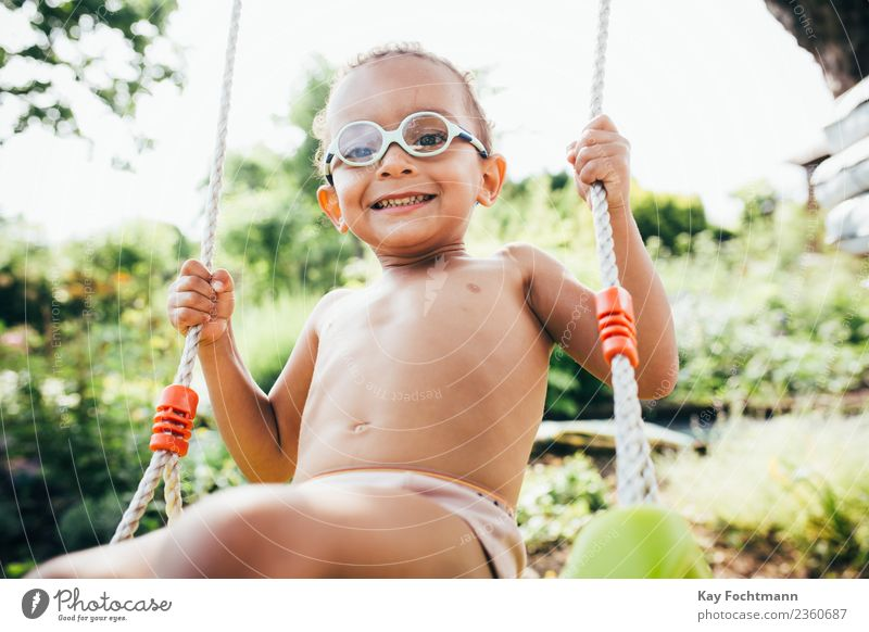 Cute black boy having fun on a swing in his parents garden Lifestyle Freude Sommer Mensch Kleinkind Junge Familie & Verwandtschaft Kindheit Leben 1 1-3 Jahre