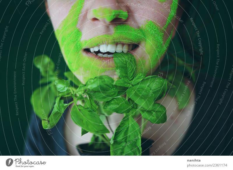 Junge Frau beißt auf ein Basilikumblatt. Lebensmittel Gemüse Ernährung Essen Bioprodukte Vegetarische Ernährung Stil Design exotisch Haut Gesicht Mensch feminin