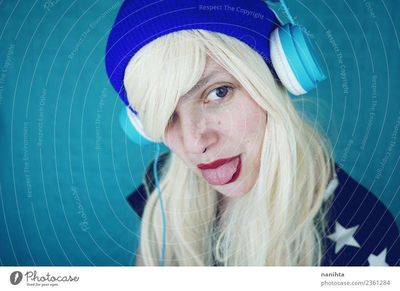 Youung Frau, die ihre Zunge herausstreckt. Lifestyle Stil Freude Haare & Frisuren Gesicht Freizeit & Hobby Headset Kopfhörer Technik & Technologie
