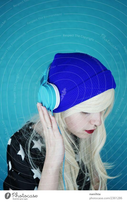 Junge blonde Frau beim Musikhören vor blauem Hintergrund Lifestyle Stil Design Haare & Frisuren Freizeit & Hobby Headset Technik & Technologie