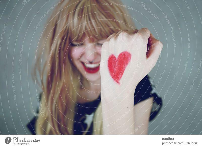 Fröhliche junge Frau mit einem roten Herzen in der Hand. Lifestyle Stil Design Freude Glück Haare & Frisuren Wellness Leben Mensch feminin Junge Frau