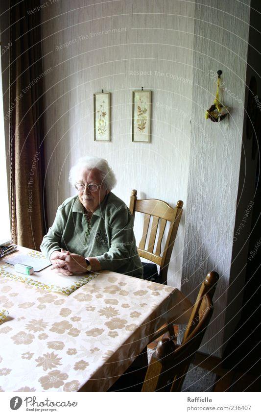 Zuhause V Frau alt Hand Erwachsene Senior Kopf Denken braun Wohnung warten sitzen Uhr Tisch authentisch Häusliches Leben Brille