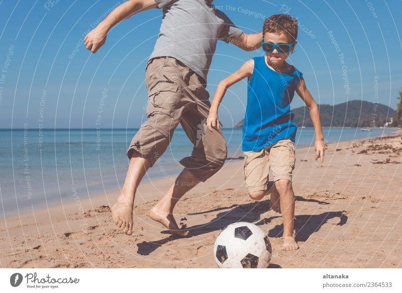 Vater und Sohn spielen tagsüber Fußball am Strand. Lifestyle Freude Glück Leben Erholung Spielen Ferien & Urlaub & Reisen Ausflug Abenteuer Freiheit Camping