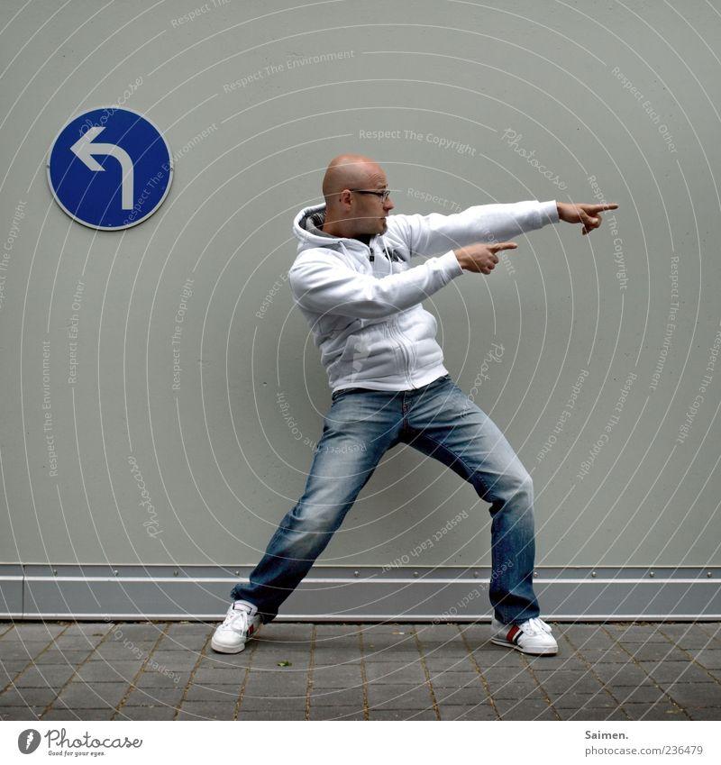 unruhestifter Mensch Mann Jugendliche Erwachsene Wand Mauer Fassade maskulin stehen 18-30 Jahre Jeanshose Pfeil Richtung zeigen Glatze Turnschuh
