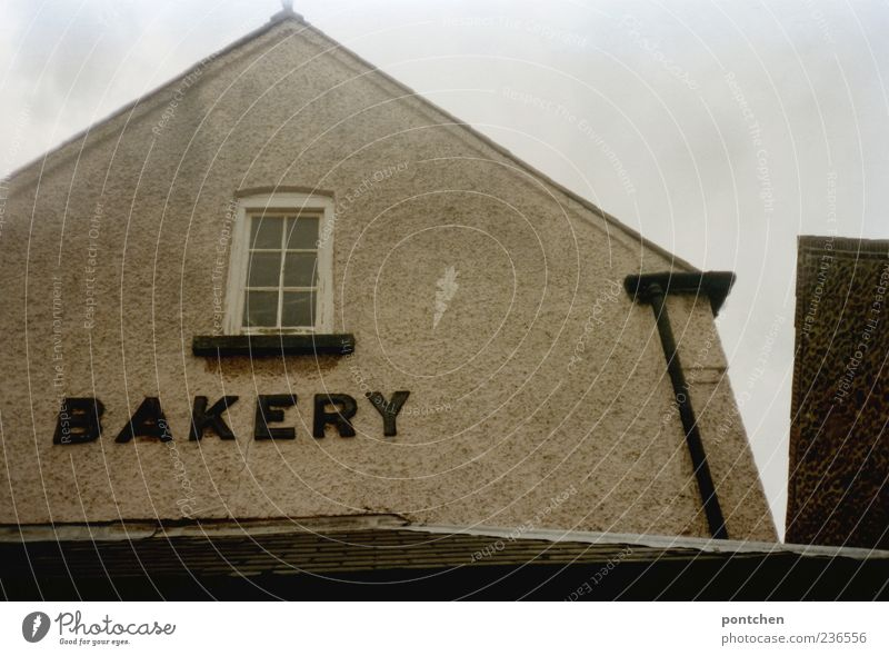 Ein altes Haus mit Aufschrift bakery Himmel Wolken schlechtes Wetter hunstanton England Dorf Bauwerk Gebäude Architektur Dach Dachrinne Englisch Wort Fenster