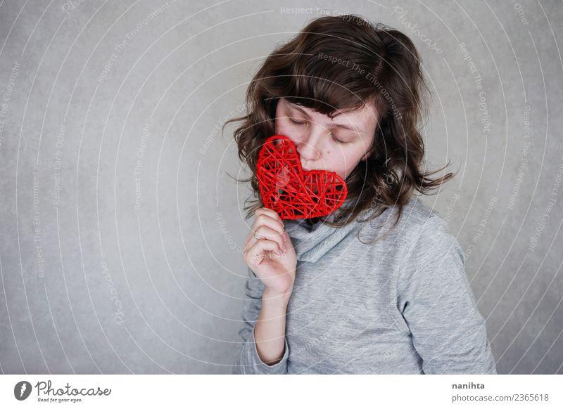 Junge Frau mit einem roten Herzen Design Gesundheit Wellness harmonisch Sinnesorgane Erholung ruhig Mensch feminin Jugendliche 1 18-30 Jahre Erwachsene brünett