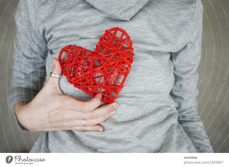 Junge Frau hält ein rotes Herz an ihrer Brust. Design Gesundheit Gesundheitswesen Wellness Leben Valentinstag Muttertag Mensch feminin Jugendliche Erwachsene 1