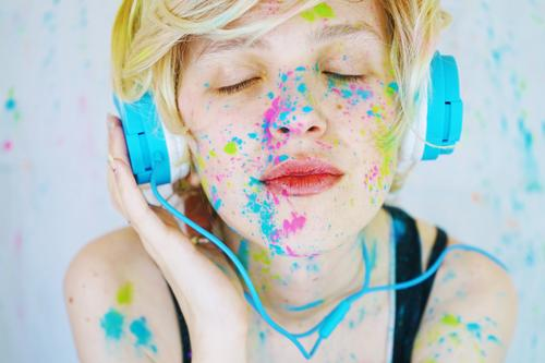 Junge Frau hört Musik mit Farbe im Gesicht. Lifestyle Stil schön Wellness Freizeit & Hobby Headset Technik & Technologie Unterhaltungselektronik Mensch feminin
