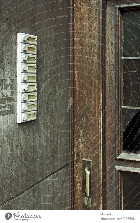 Eingang Haus Mehrfamilienhaus Tür Namensschild Klingel Holz Glas braun grau Einsamkeit Wohnungssuche Wohnungssituation Leerstand Farbfoto Gedeckte Farben