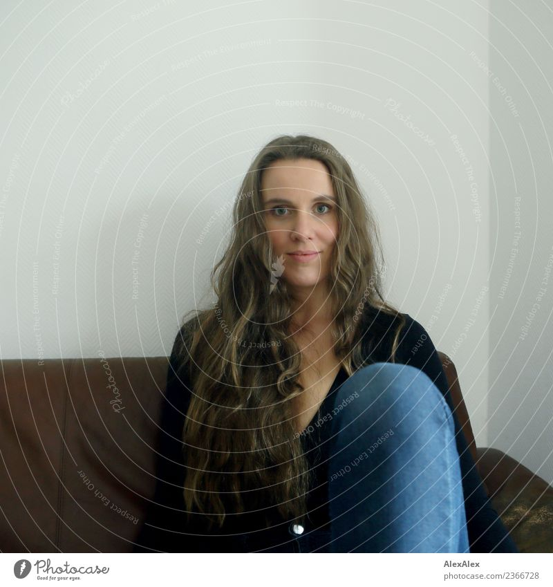 Portrait einer Frau, die auf einem braunen Sofa sitzt Stil schön Leben Wohlgefühl Junge Frau Jugendliche Gesicht Knie 18-30 Jahre Erwachsene Jeanshose Top